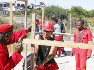 HELPING HAND: EFF provincial spokesman Nazier Paulsen helps to erect a shack during the land invasion in Khayelitsha. Photo: Bheki Radebe